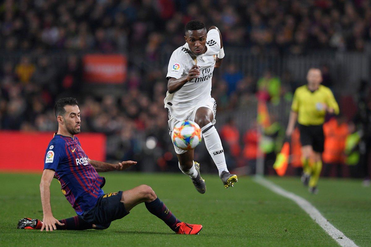 Pemain Real Madrid Vinicius Junior menghindari tekel Gelandang Barcelona Sergio Busquets.