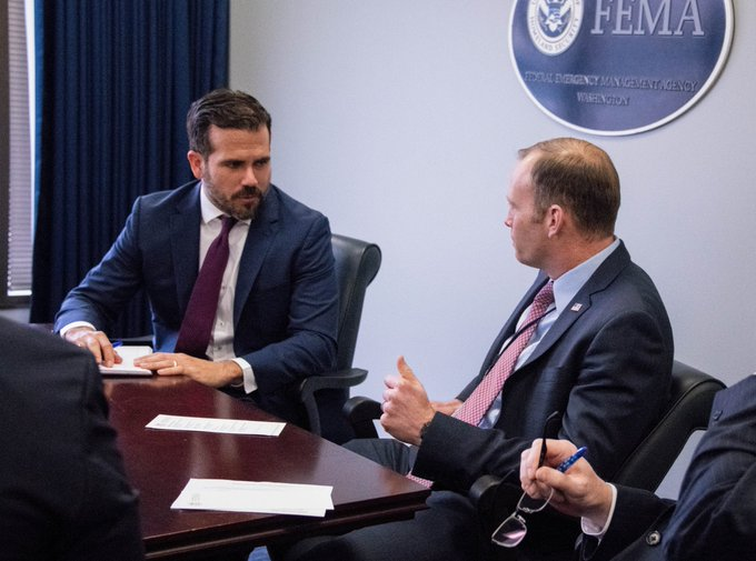 FEMA Administrator Brock Long is shown sitting at a desk meeting with Puerto Rico Governor Ricardo Rossello in Washington, D.C.