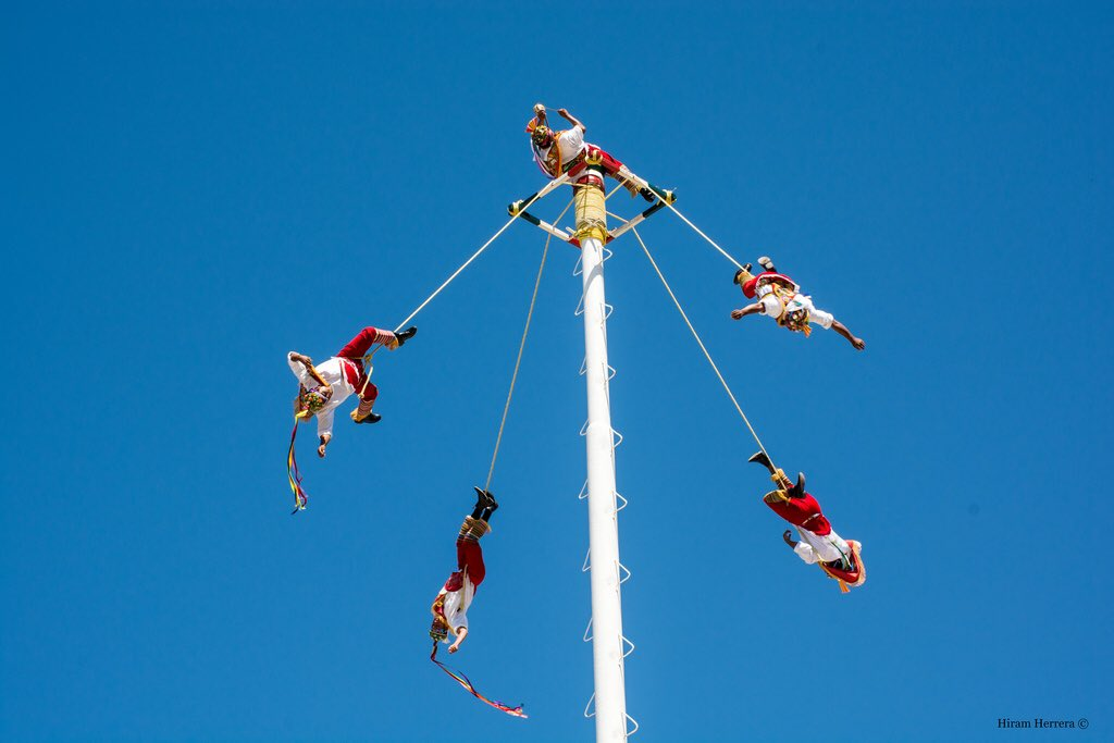 It's a ritual used to end droughts in which five performers climb a 100 foot pole. Once at the top, one of them dances untethered on top playing the drums and flute, while the other four descend via ropes headfirst, swinging around the pole until they reach the ground.