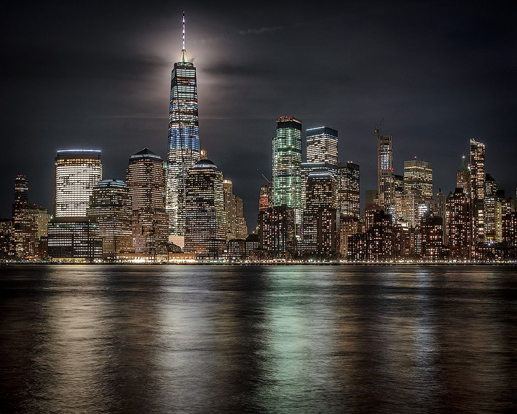 The World Trade Center glows as the full moon passes behind it Tuesday evening.