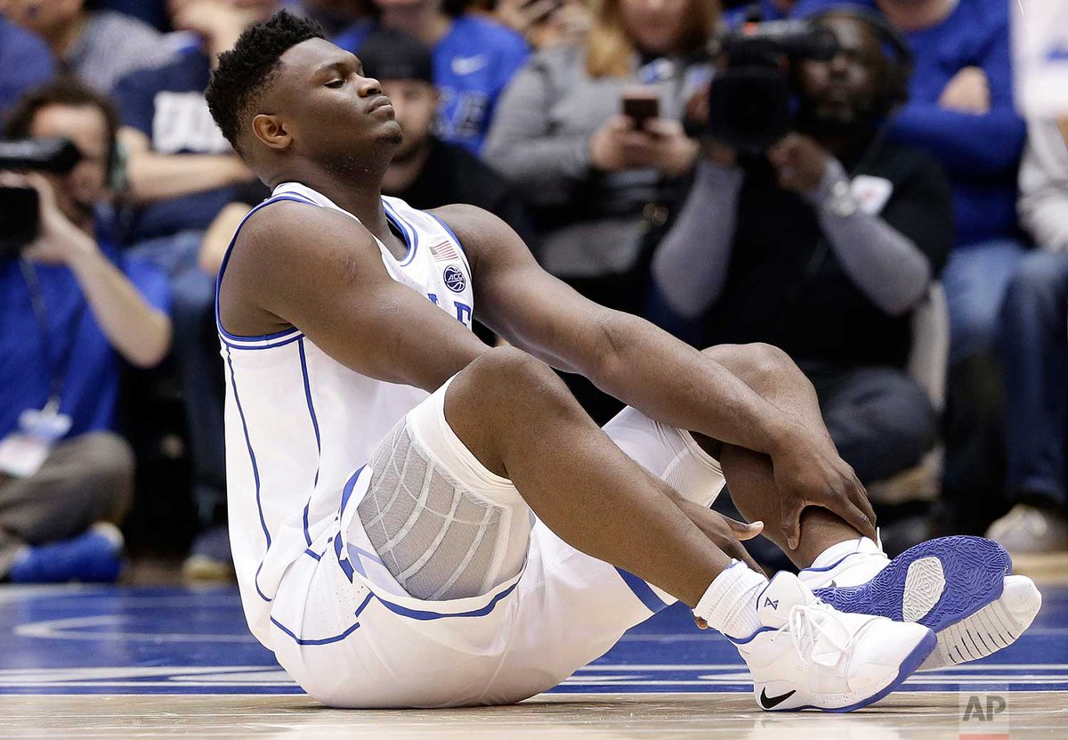 Duke's Zion Williamson sits on the floor following a injury during the first half of an NCAA college basketball game yesterday against North Carolina in Durham, N.C. (AP Photo/Gerry Broome)
