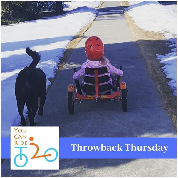 A sunny Alberta day with snow still on the ground, a young child (wearing a red helmet) is riding away on an adapted trike along a clear sidewalk - accompanied by their dog!
