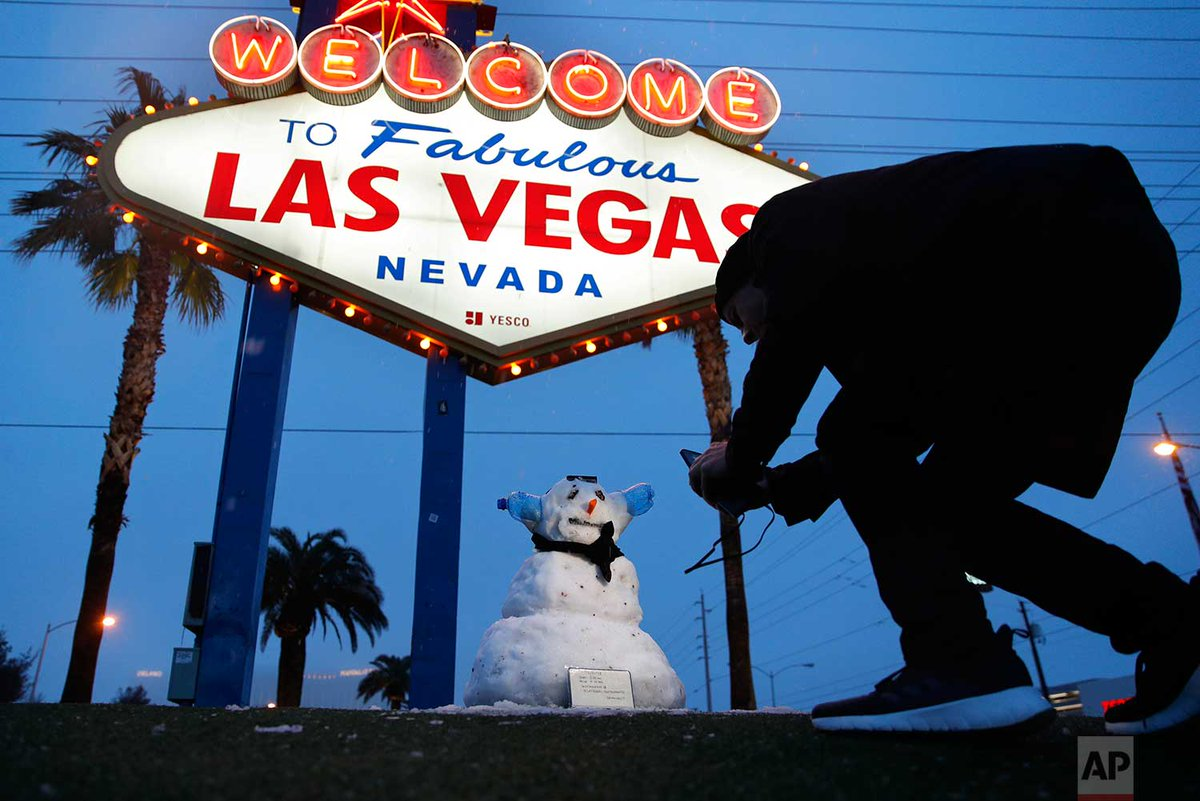 """A man takes a picture of a small snowman at the """"Welcome to Fabulous Las Vegas"""" sign along the Las Vegas Strip today in Las Vegas. 