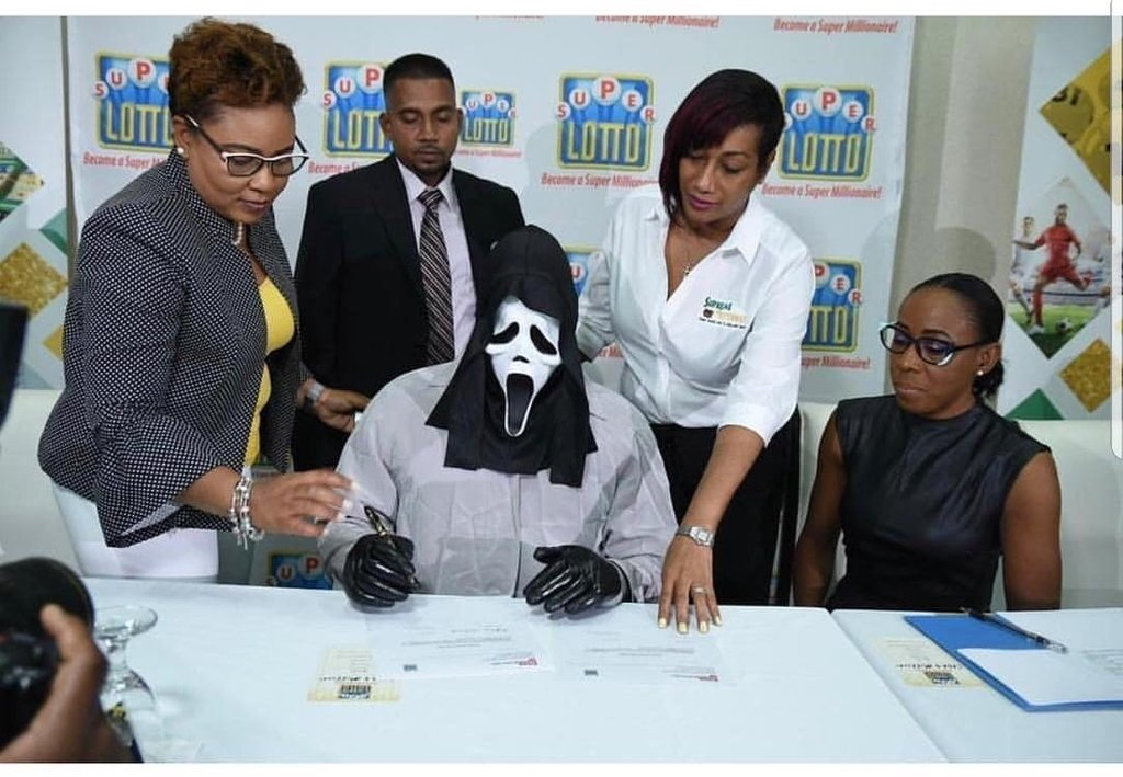 IMAGE: Jamaican lotto winner trying to hide his identity at prize ceremony.   (Source: Jamaica Star)