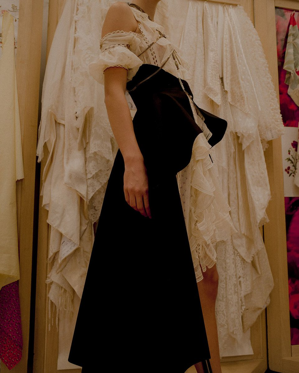 An ivory silk knit dress with laddered ruffle trims and lacing details, worn with an asymmetrical draped belt. Photographed during fittings in London. Discover more: https://t.co/b7519aHhbX #McQueenSS19  #AlexanderMcQueen