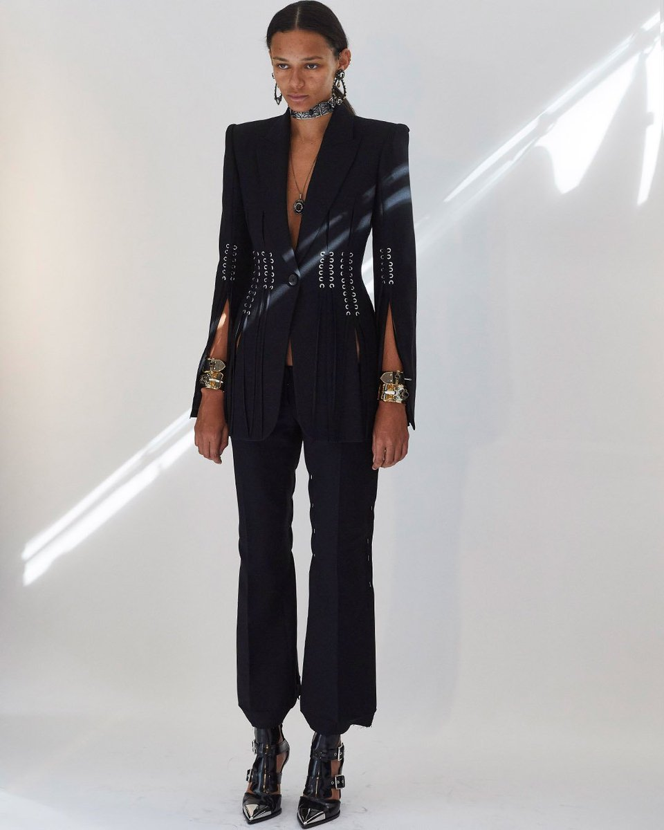 A black wool silk jacket, slashed, pieced and laced with metal eyelets, worn with kickback bumster trousers. Photographed by #SirDonMcCullin at the Spring/Summer 2019 show. Discover: https://t.co/b7519aHhbX #McQueenSS19  #AlexanderMcQueen