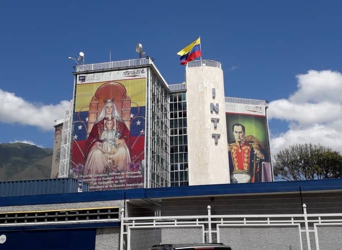 SE CAEN LOS SIMBOLOS DE LA NARCODICTADURA En el INTTT en su sede la California, Caracas las paredes exibian dos gigantografías, la de Chávez y la de Maduro. Las susttuyeron y pusieron en su lugar a la Virgen de Coromoto Nuestra Patrona y el retrato original de BOLIVAR