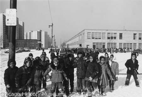 Children outside Crispus Attucks Elementary at 38th and Dearborn. 1959. Photographer Clarence W. Hines.