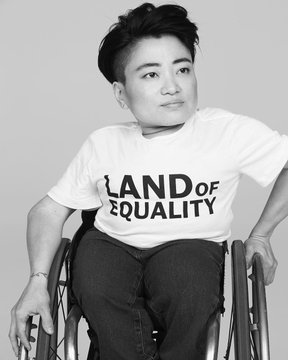 Black and white photo of me in my wheelchair in a Land of Equality t-shirt.