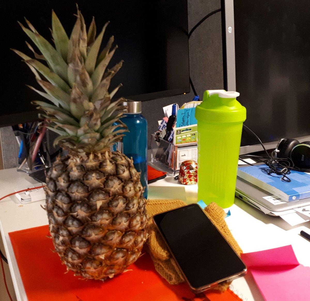 Työpöydällä toimistotarvikkeita sekä tuore ananas.