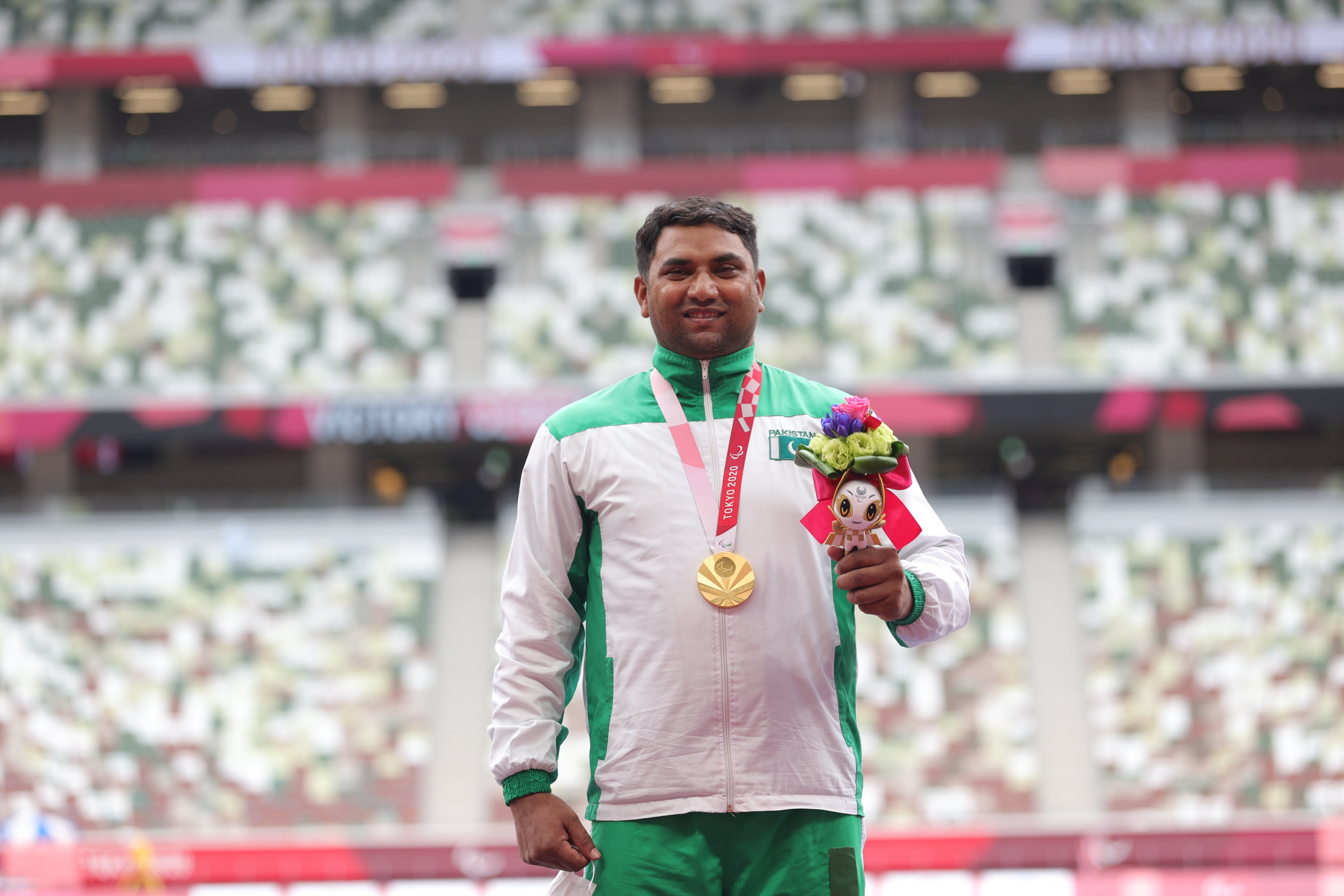 A photo of Pakistani athlete Haider Ali after receiving his gold medal. He is wearing his medal around his neck, holding the Someity mascot and smiling.