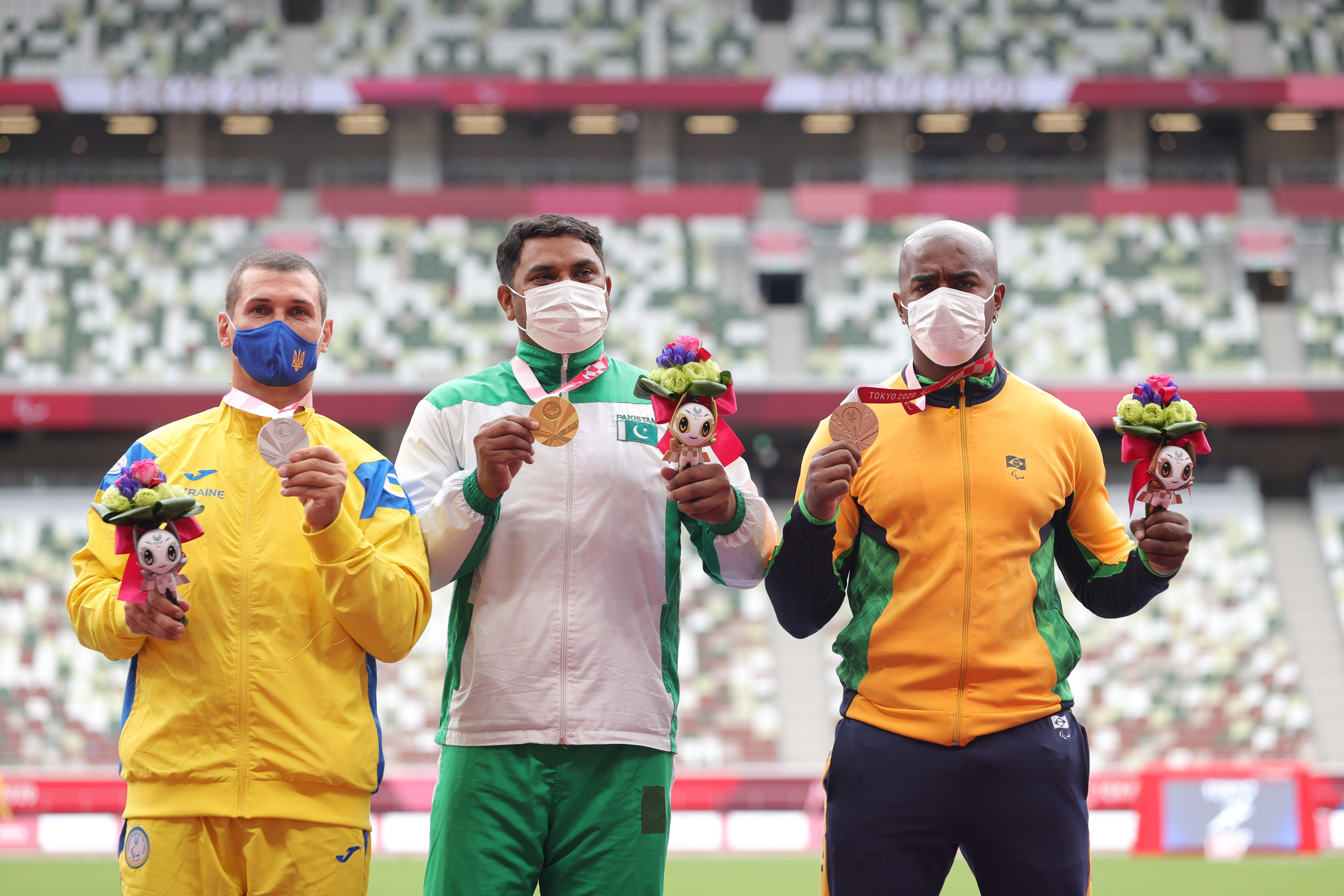 The three discus medallists on the podium. They are holding up their medals and wearing masks.