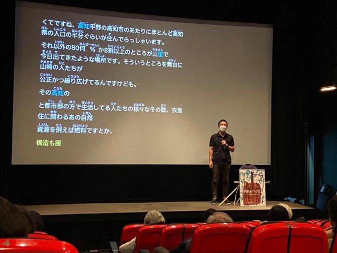 舞台上の劇場スクリーンの前に立ち、トークをする今井監督。スクリーンには、監督が話した言葉が文字としてリアルタイムで表示されている。
