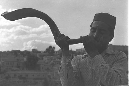 صورة من عام 1959 لرجل يهودي يمني ينفخ في البوق (الشوفار) على جبل صهيون في أورشليم في رأس السنة العبرية. …