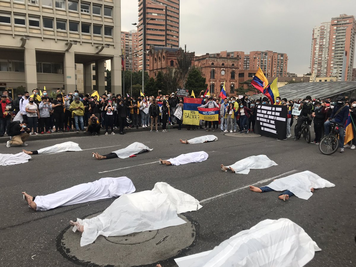 A group of demonstrators block a road in Bogota to protest against those who have lost their lives at the hand of the police during the ongoing protests in 🇨🇴. They lay on the road with white sheets over them and name tags on their toes to represent those who have died. https://t.co/f5ZLnIfqd6