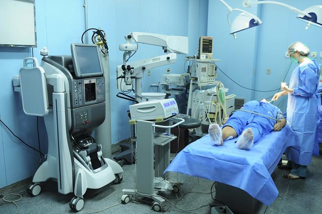 imagem de uma sala de hospital com com vários equipamentos, uma pessoa deitada na maca e um médico ao lado fazendo atendimento
