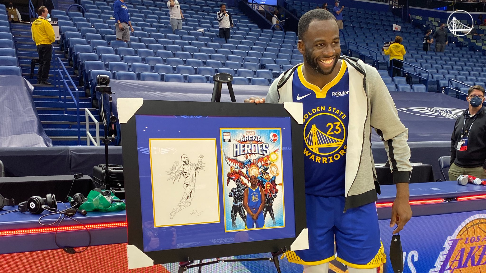 Draymond poses next to the Arena of Heroes champion poster