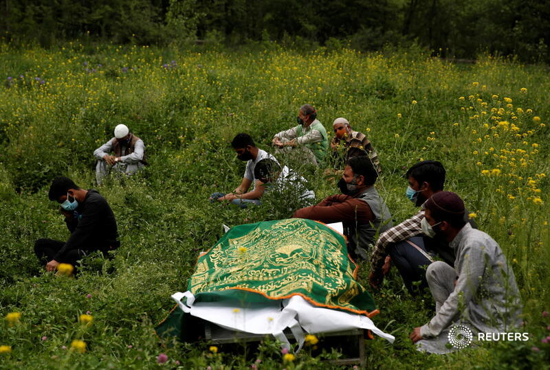 Relatives sit next to the body of a man who died of the coronavirus, as they wait for a grave to be prepared for his burial on the outskirts of Srinagar. More photos of the day: https://t.co/XN6Y89c7EY 📷 @900Danishismail https://t.co/8IW8Icait3