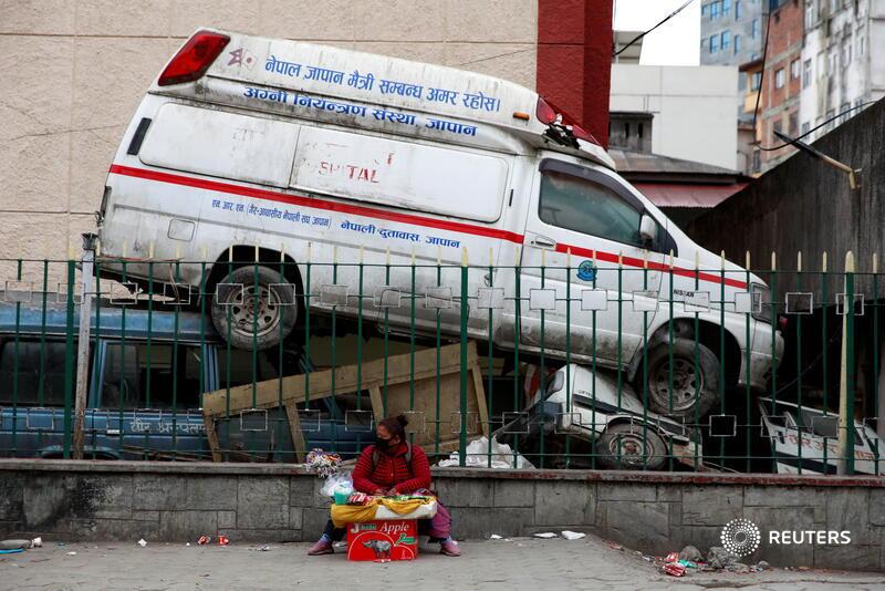 A street vendor sits next to an abandoned ambulance outside a hospital in Kathmandu, amid Nepal's second coronavirus wave. More photos of the day: https://t.co/u1pu9qFAJp 📷 @NaveshChitrakar https://t.co/kc7kdLEYzT