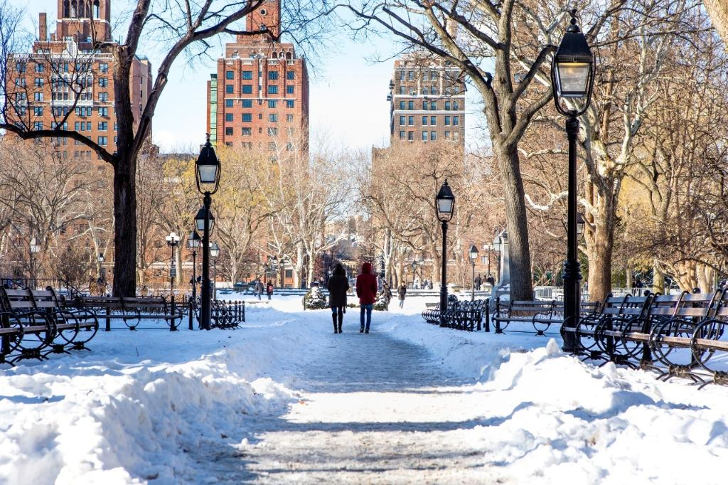 Two students walking through a snowy Washington Square Park on a bright sunny day