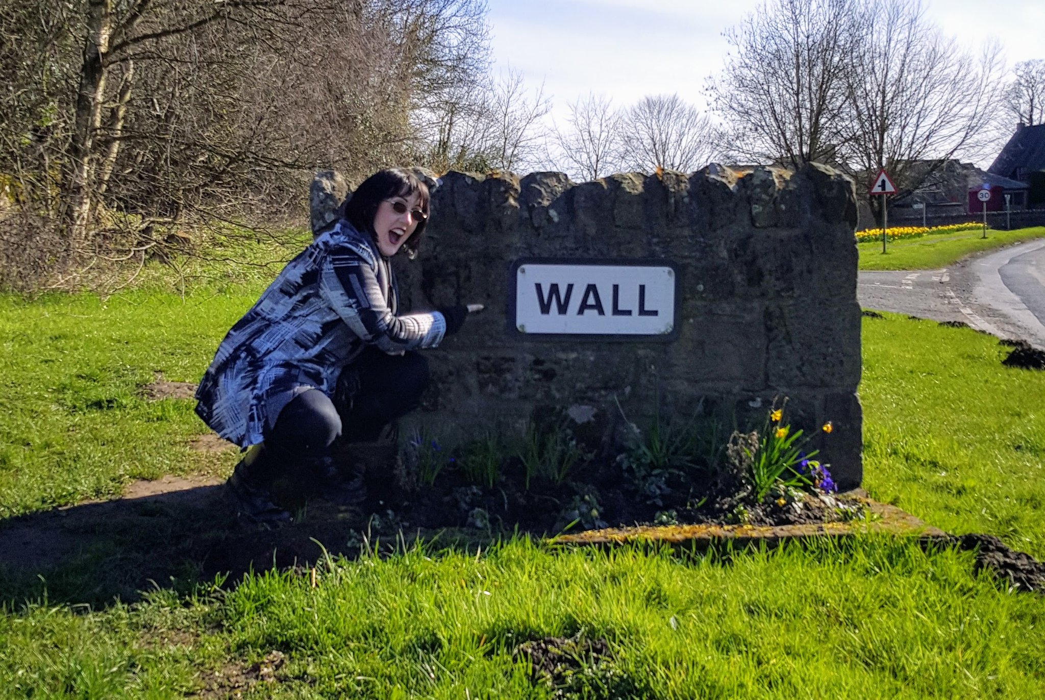 An image of Icy posing next to the village sign for Wall in Northumberland.