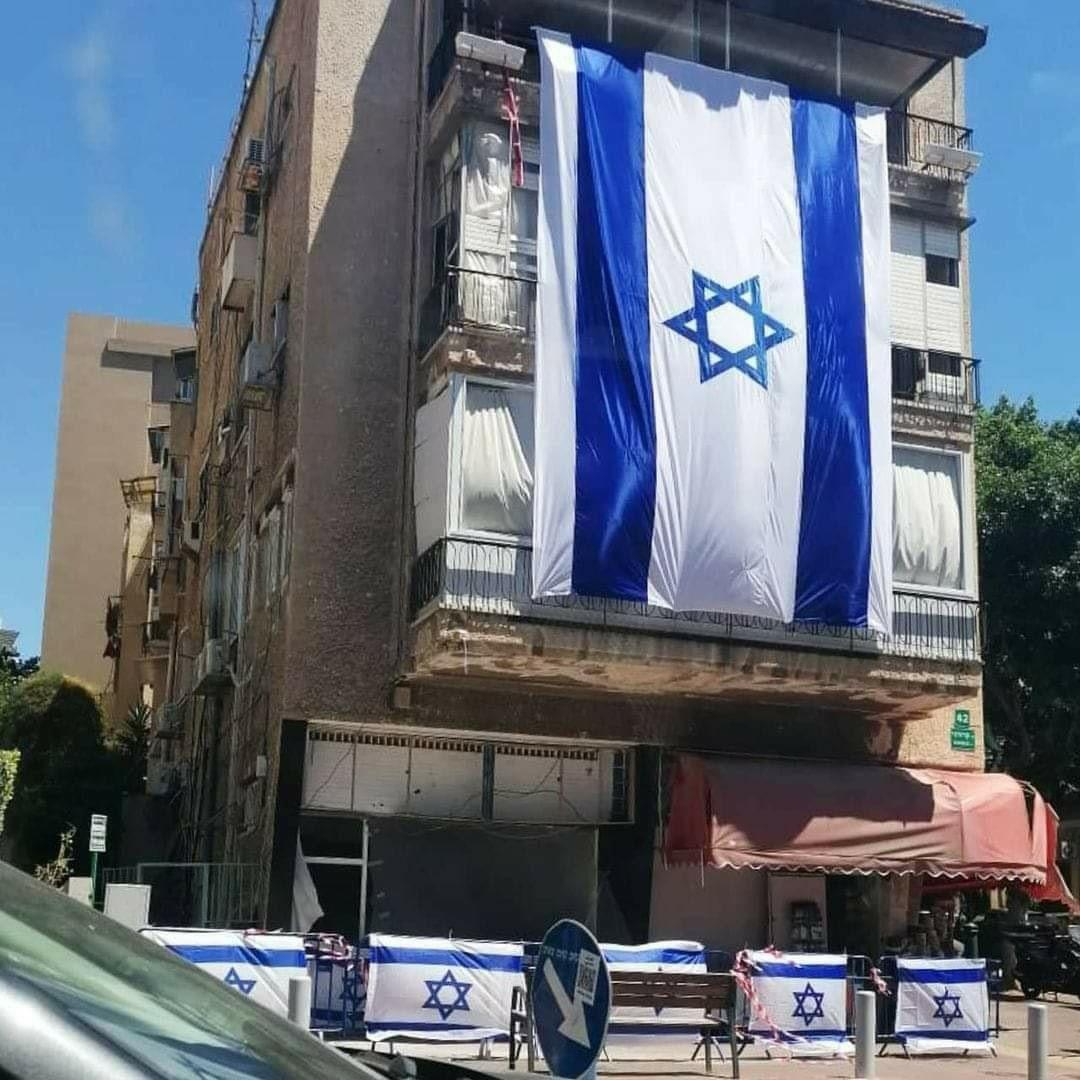 العلم الإسرائيلي يرفرف على مبنى سكني تعرض لهجوم صاروخي إرهابي, مهما حاولوا لن يكسروا إرادتنا لان شعب اسرائيل حي