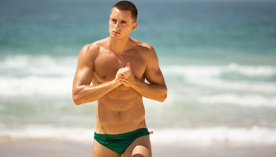 Photo of a man wearing green swimming trunks on a beach with the sea in the background.