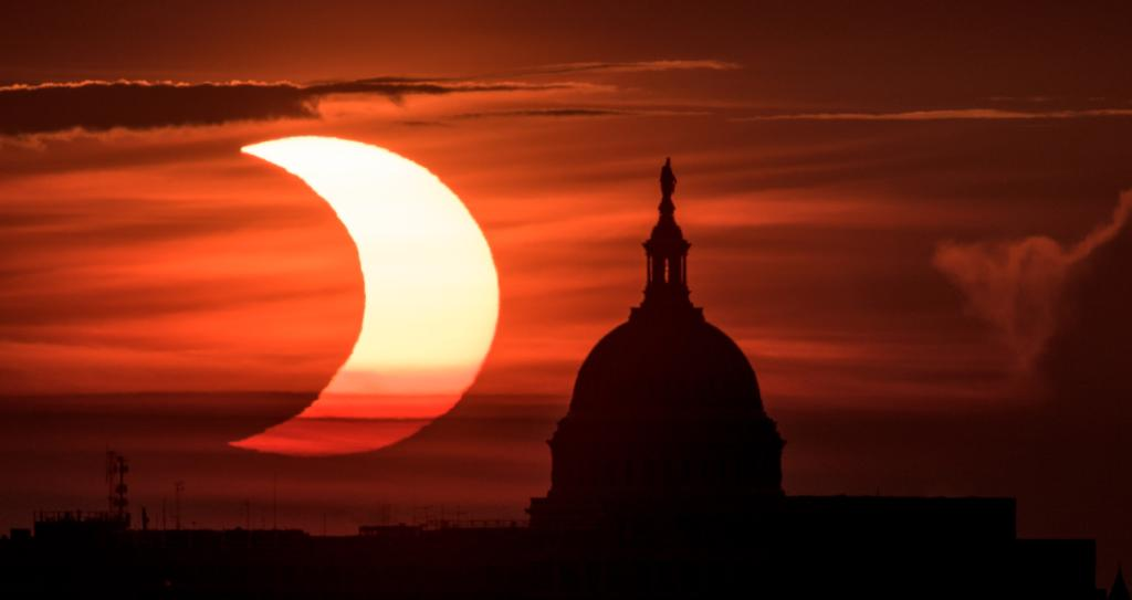 A partial solar eclipse is seen duing sunrise behind the US Capitol