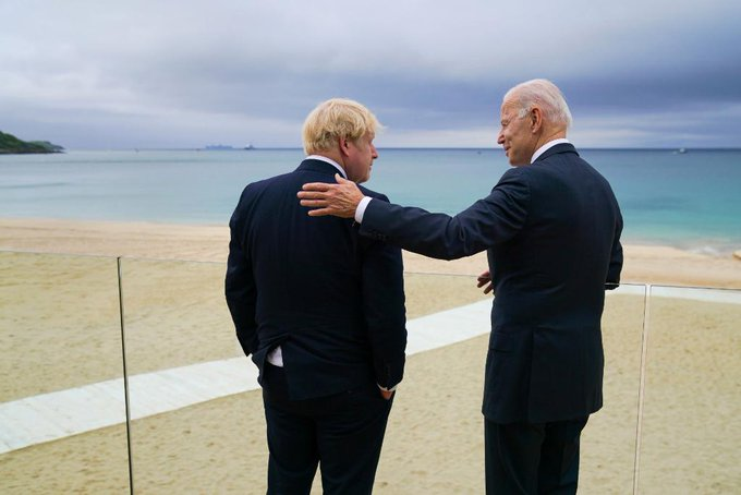 President Biden and Prime Minister Johnson talk while overlooking the water.