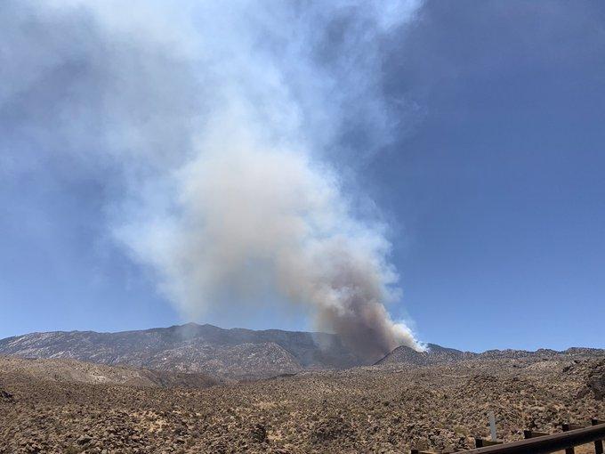A smoke plume rises out of a mountainous area.