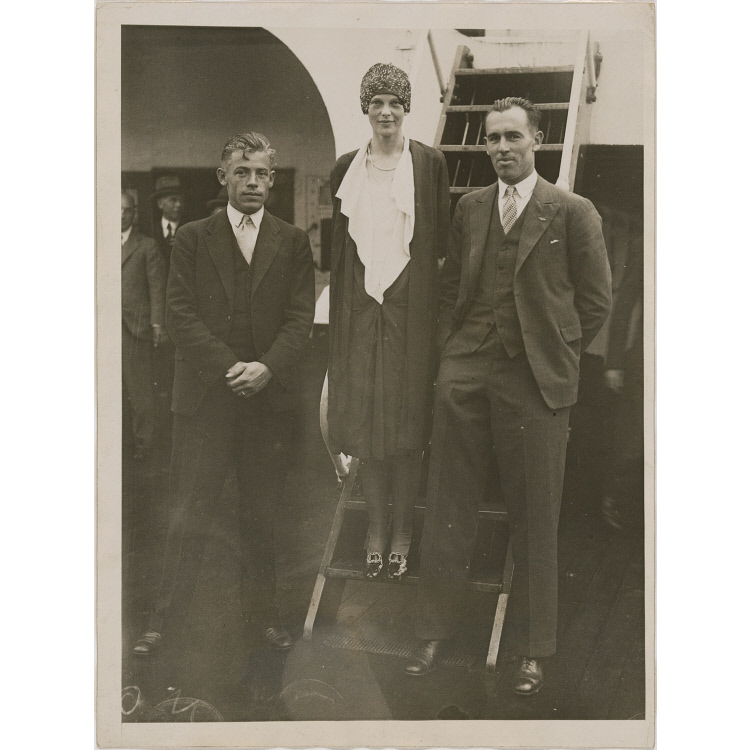 """Wilmer """"Bill"""" Stultz (left), Amelia Earhart (middle), Louis """"Slim"""" Gordon (right) stand for a photo in front of the aircraft steps."""