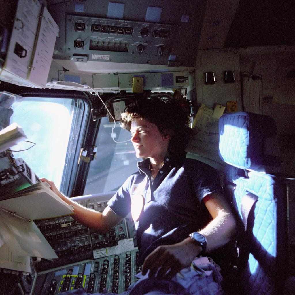 Sally Ride monitors the control panels on Space Shuttle Challenger's flight deck.