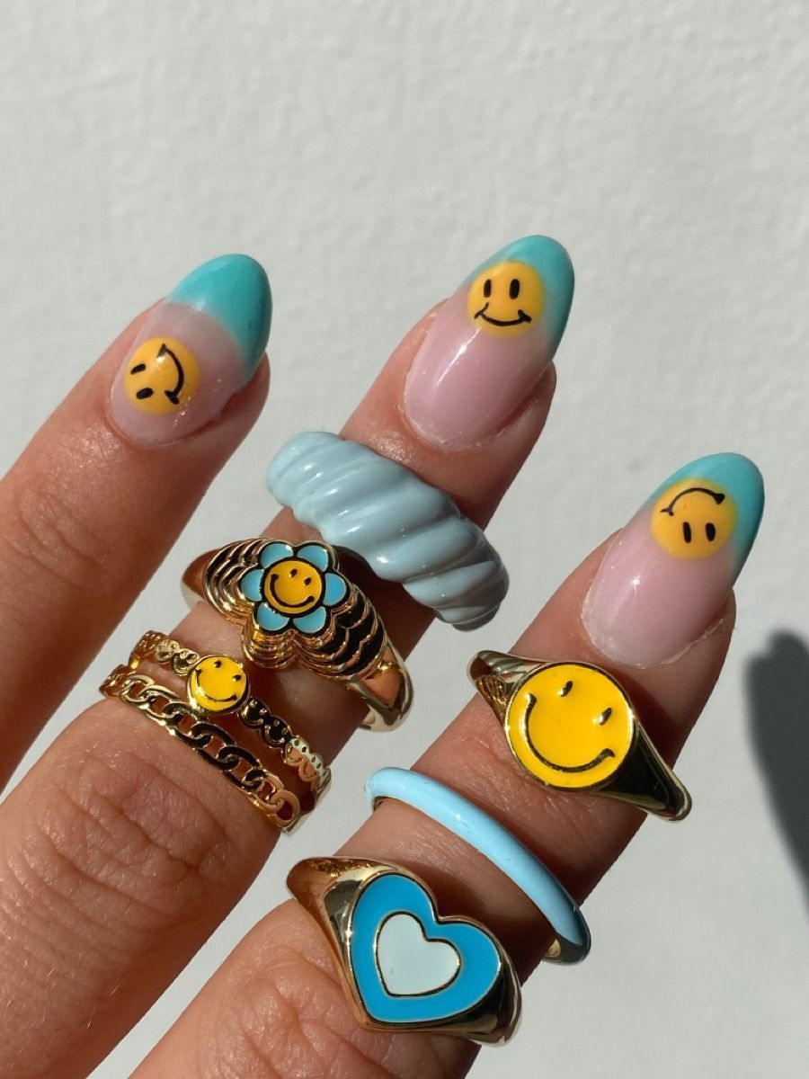close up of manicure with blue tips and yellow smiley faces dotted on them. Matched with blue and gold jewellery