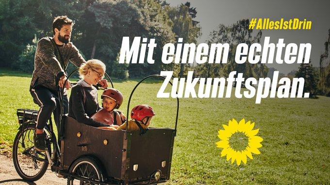 Ein Mann fährt ein Lastenrad, in dem vorne eine Frau und zwei Kinder drin sitzen.