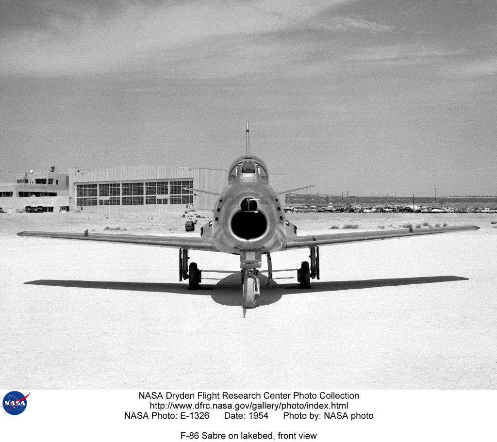 F-86 Sabre on lakebed, front view with High-Speed Flight Station in the background