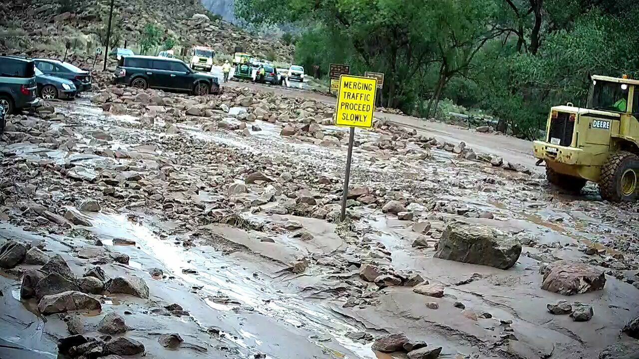 """Mud and rocks cover the road. A yellow sign reads """"Merging traffic proceed slowly""""."""