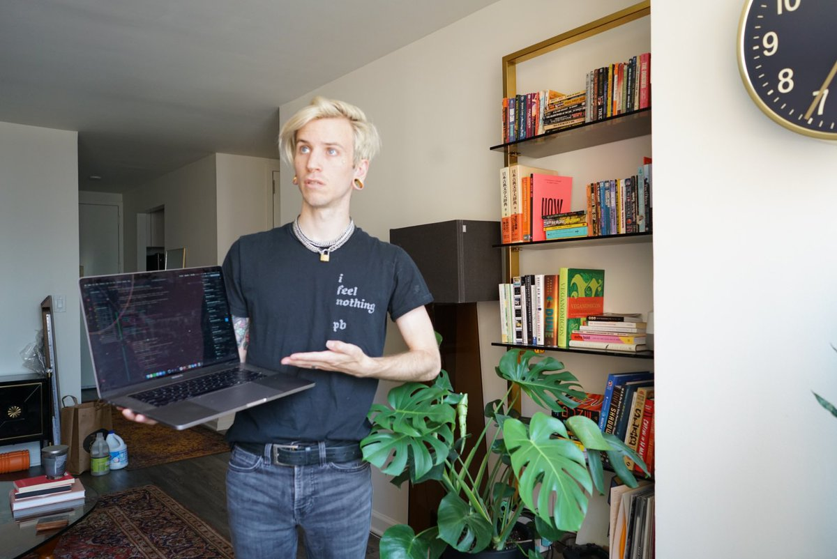 A web designer holding a laptop showing off his newest design on a laptop.