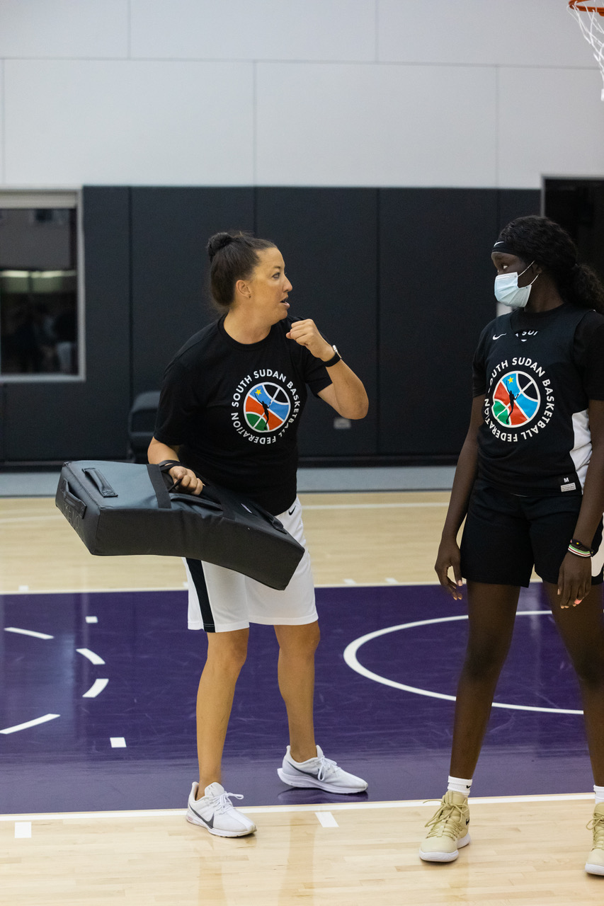 UC Davis associate head coach Des Abeyta is going through drills with a member of the South Sudan Women's National Team as they prepare for their first international tournament.