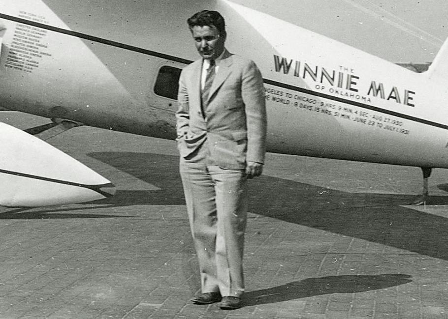 Wiley Post standing in front of his Winnie Mae.