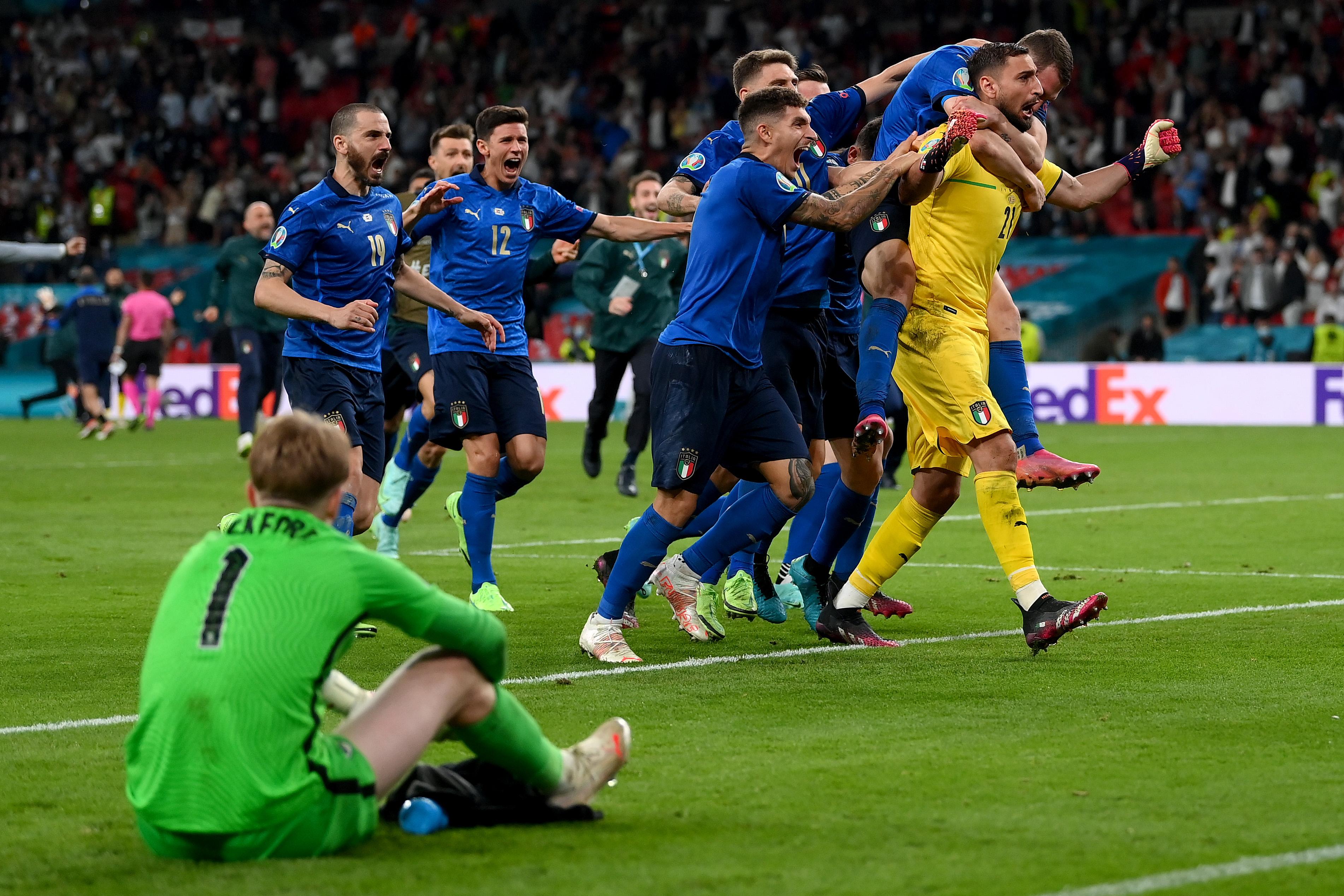 Kiper Inggris Jordan Pickford duduk lesu di lapangan usai timnya kalah adu penalti.