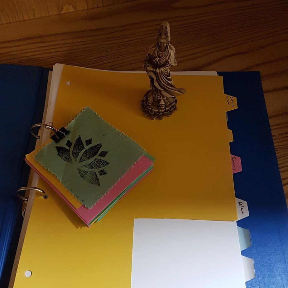 A folder with tabs on it.  There is a statue of Quan Yin on the folder and a number of coloured cue cards with a lotus patch all pinned together.