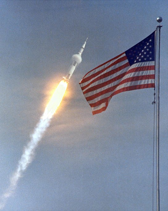 Saturn V rocket launch with American Flag in foreground.