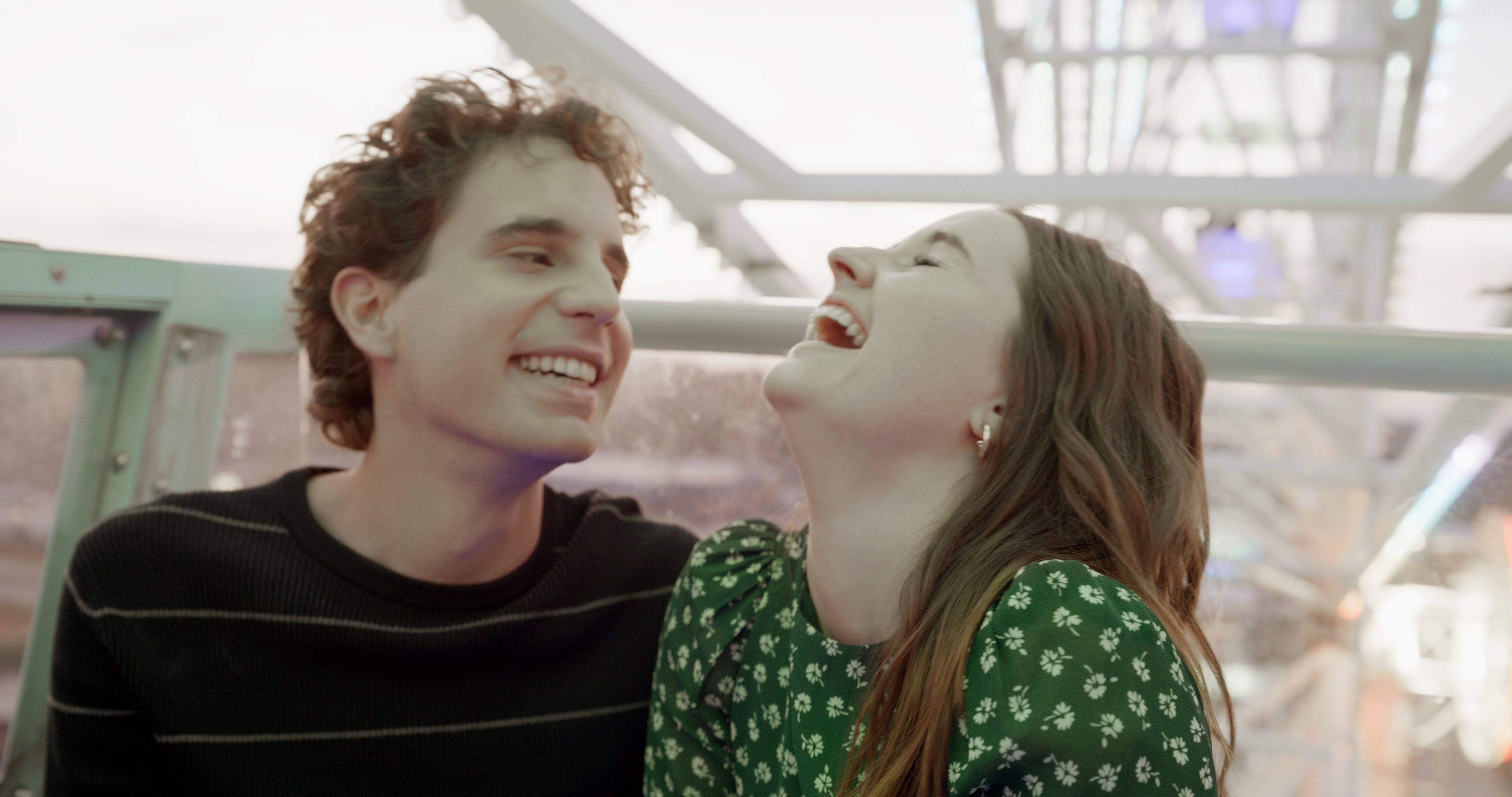 Ben Platt and Kaitlyn Dever sit together laughing, high up in a Ferris wheel carriage
