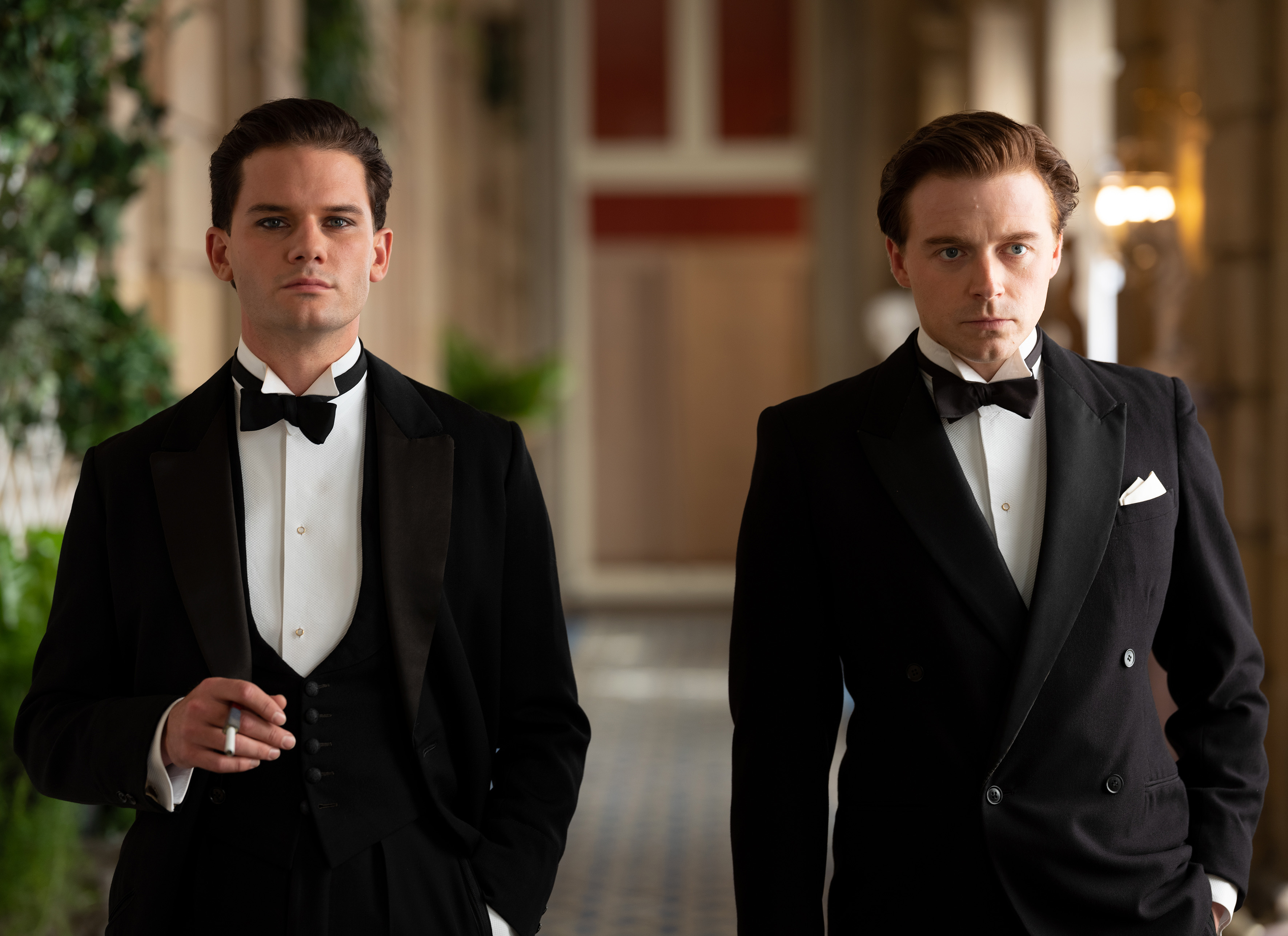 Wearing tuxedos, Jeremy Irvine and Jack Lowden stand together in a formal venue looking in the same direction out-of-frame