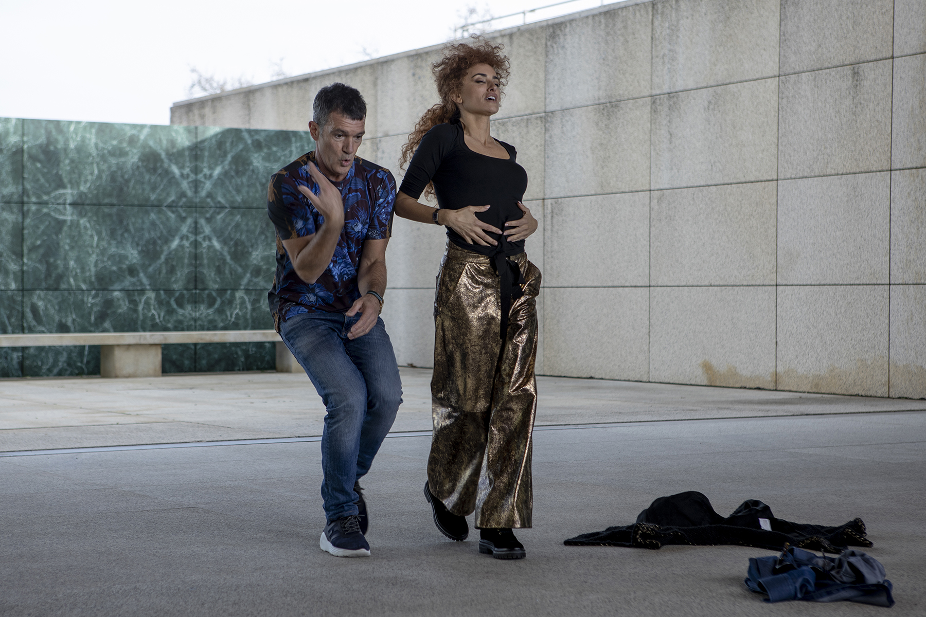 Penelope Cruz and Antonio Banderas dance together in a cement plaza with jackets on the ground
