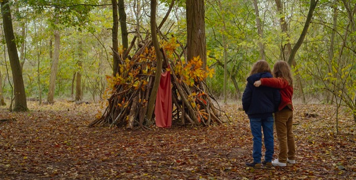 Young sisters Joséphine Sanz and Gabrielle Sanz lean on each other while looking proudly at a fort they built in an autumn forest