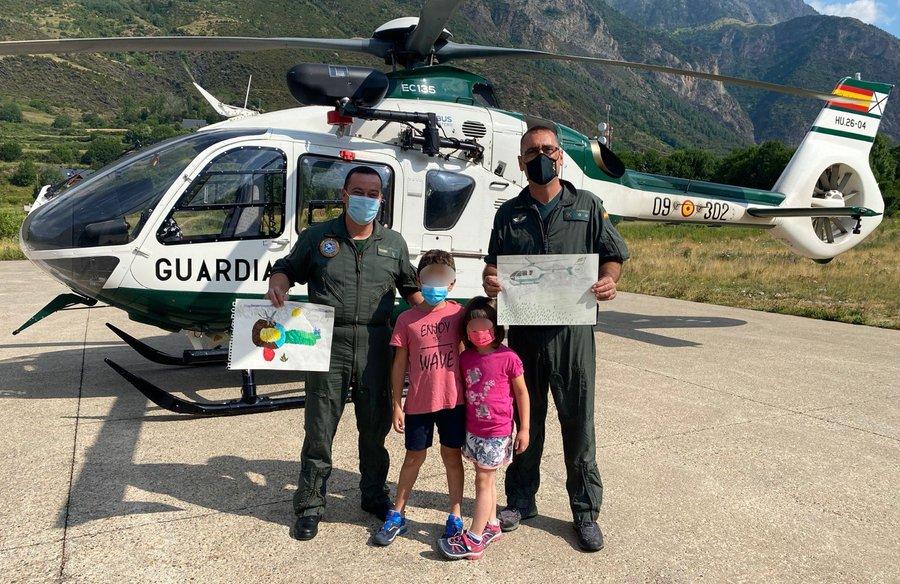 Dos pilotos del Servicio Aéreo de la Guardia Civil de Benasque posan con dos niños y los dibujos que les han regado para reconocer su servicio.