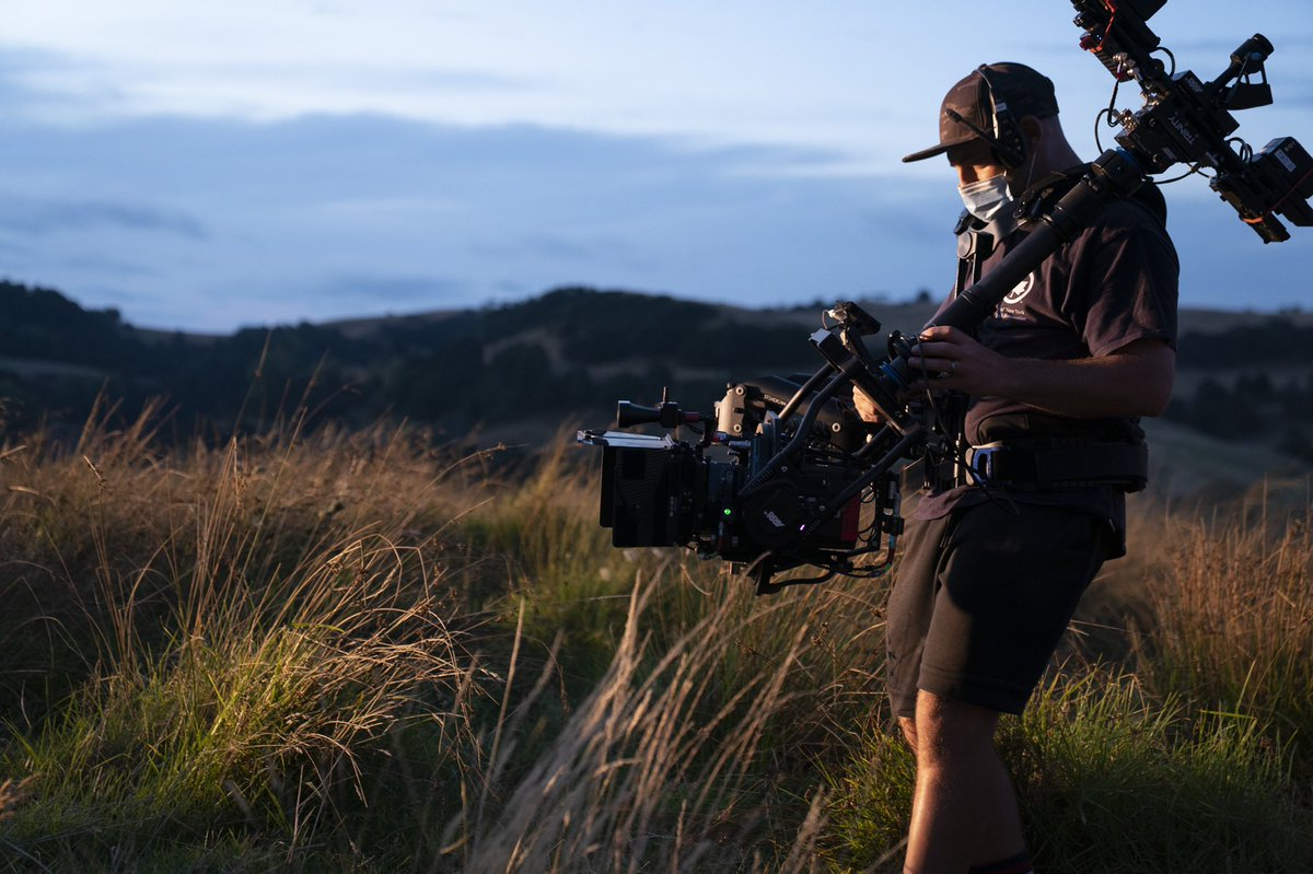 A crew member wearing all black and a face mask stands in a windswept field of tall grass in the late afternoon. He's holding a camera and is looking down into the screen. Rolling hills are in the background.