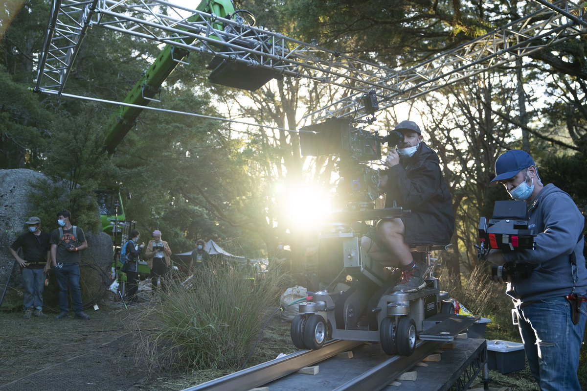 A masked crew member sits on a camera dolly behind a camera while other crew members work around them. In the forest around him, other masked crew members are hard at work. The sun peeks through the woods just above the horizon.