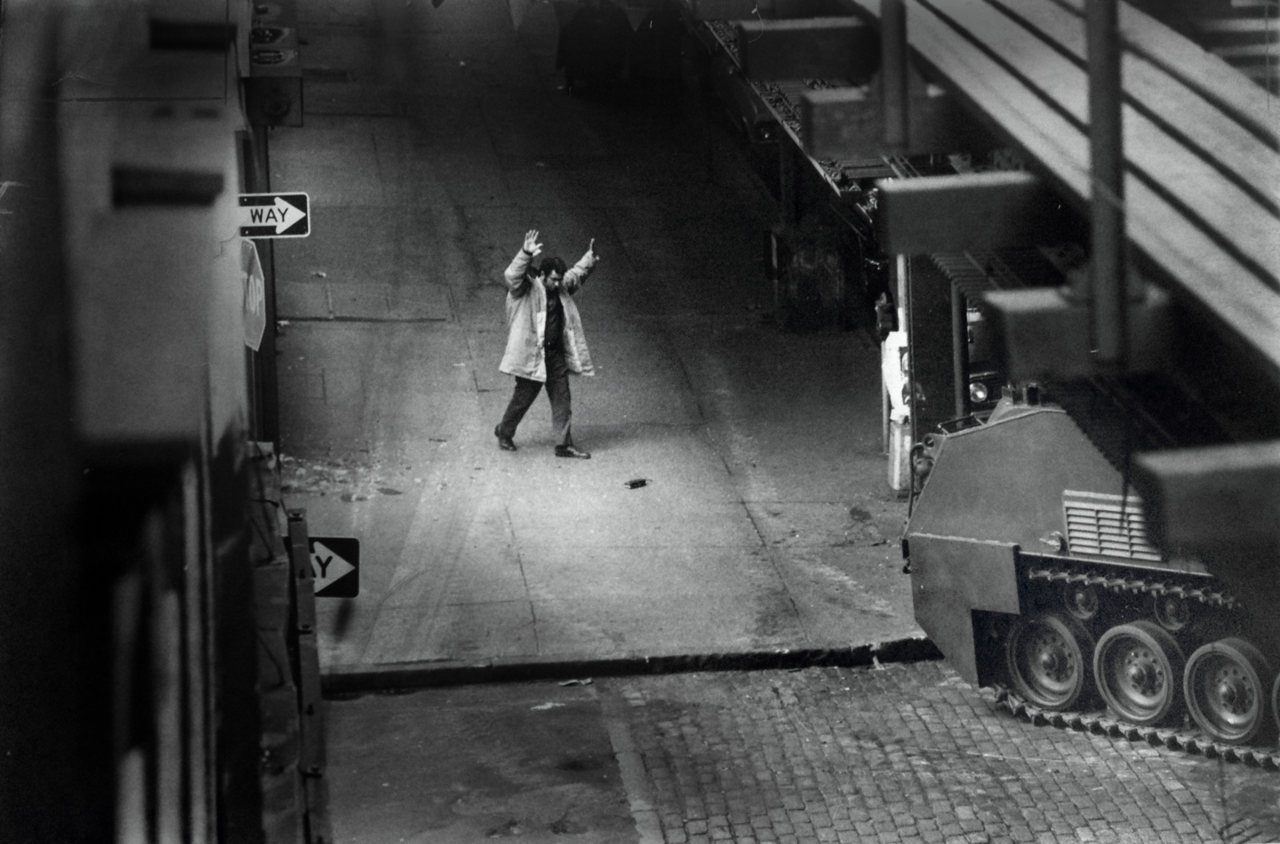 On a deserted New York street in black-and-white, a man walks towards a line of tanks with his hands held in the air.
